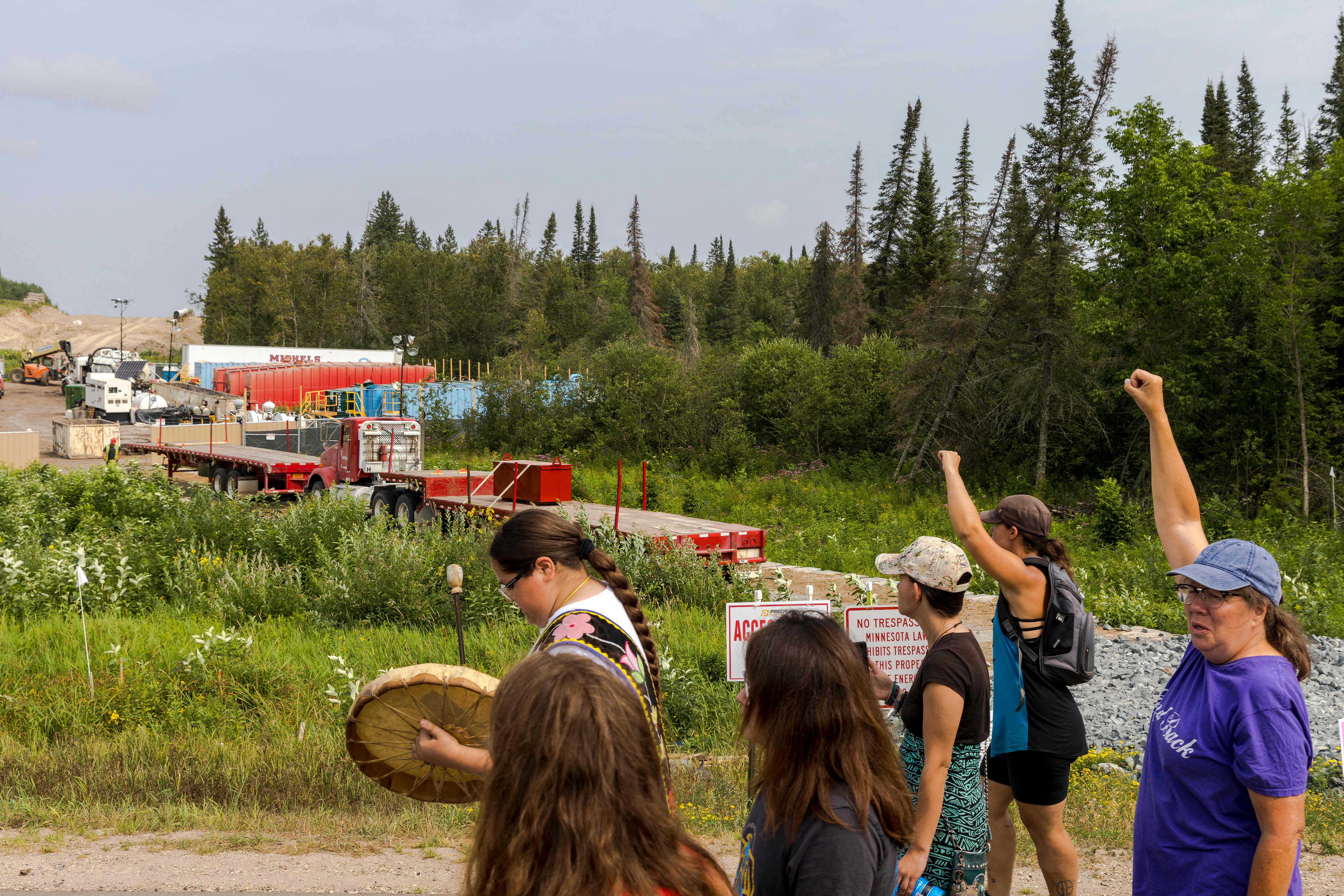 A group of Indigenous people and activists raise their fists as they pass Sections of the Enbridge Line 3 pipeline construction during the 'Treaty People Walk for Water' event near the La Salle Lake State Park in Solway, Minnesota on Aug. 7, 2021. Credit: Kerem Yucel/AFP via Getty Images
