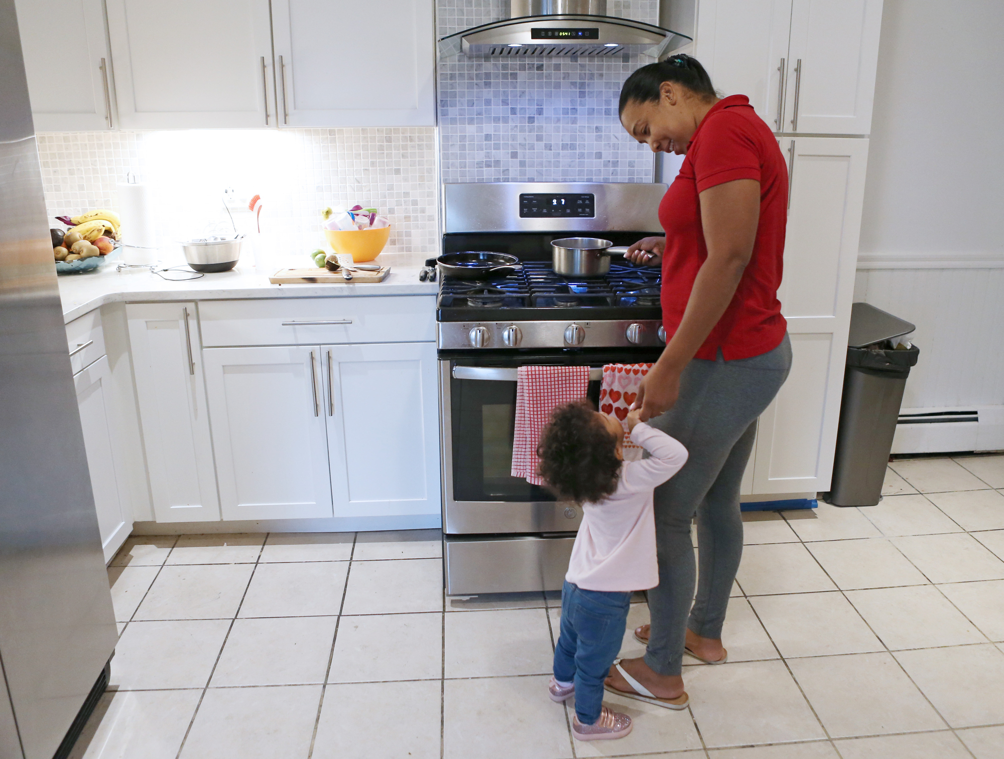 Yohanny Cespedes interacts with her daughter as she prepares breakfast on a gas stove on Sept. 12, 2019 in Lawrence, Massachusetts. Credit: Angela Rowlings/MediaNews Group/Boston Herald via Getty Images