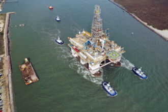 In this aerial image from a drone, tug boats tow the semi-submersible drilling platform Noble Danny Adkins through the Port Aransas Channel into the Gulf of Mexico on Dec. 12, 2020 in Port Aransas, Texas. Credit: Tom Pennington/Getty Images