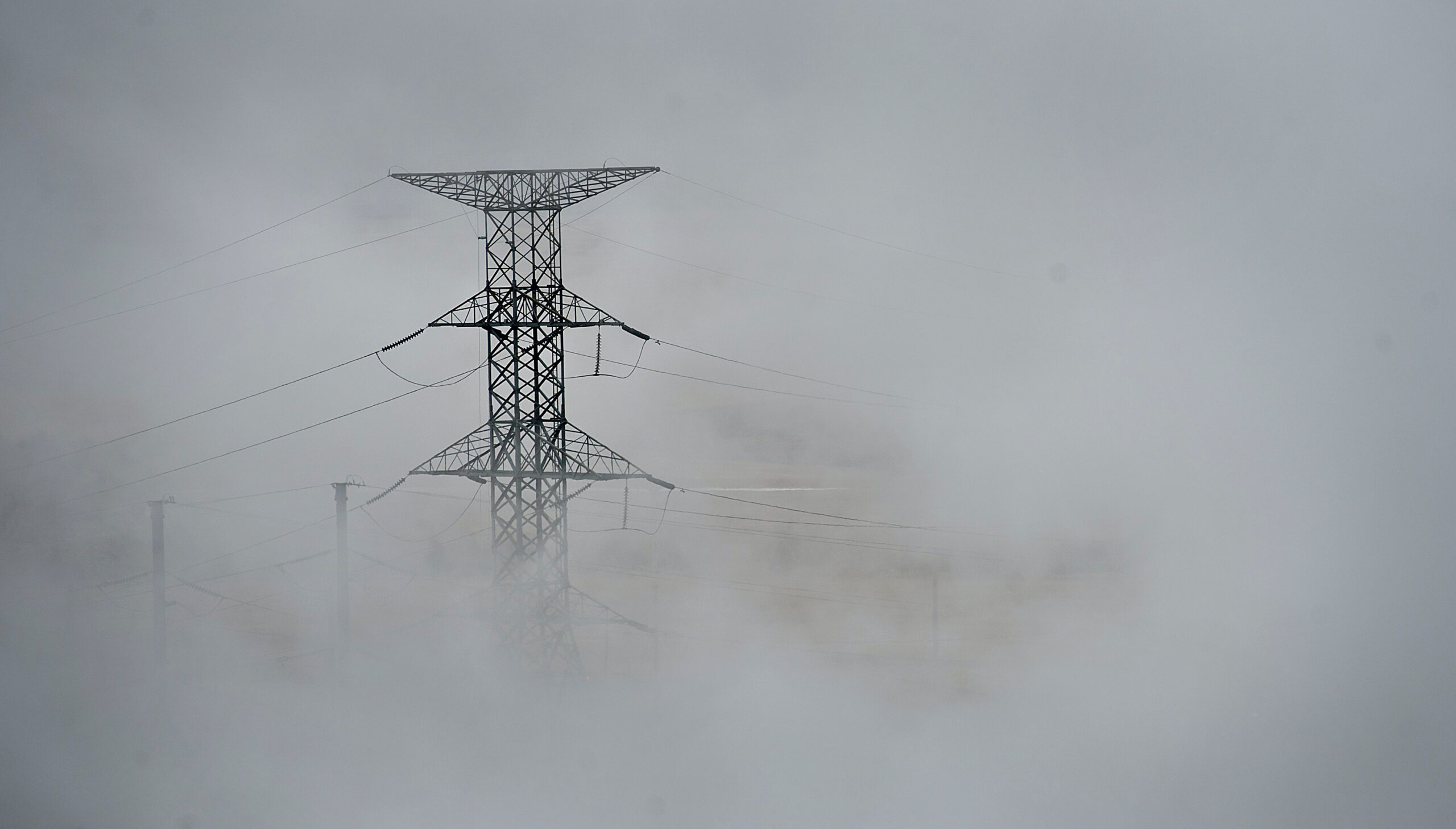 An electricity transmission tower is shrouded in steam being exhausted outside the Great River Energy Coal Creek Station power plant in Underwood, North Dakota, on Thursday, Feb. 9, 2012. Credit: Daniel Acker/Bloomberg via Getty Images