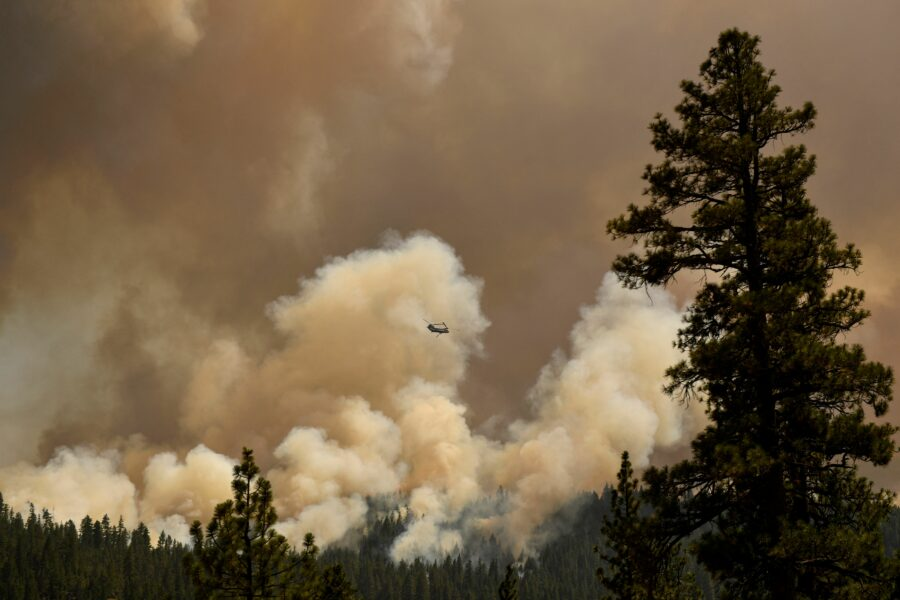 A firefighting helicopter flies past smoke plumes after making a water drop during the Dixie Fire on Aug. 18, 2021 near Susanville, California. Credit: Patrick T. FALLON/AFP via Getty Images