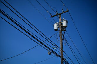 Power lines on utility poles in Smithtown, New York on June 29, 2021. Credit: Thomas A. Ferrara/Newsday RM via Getty Images