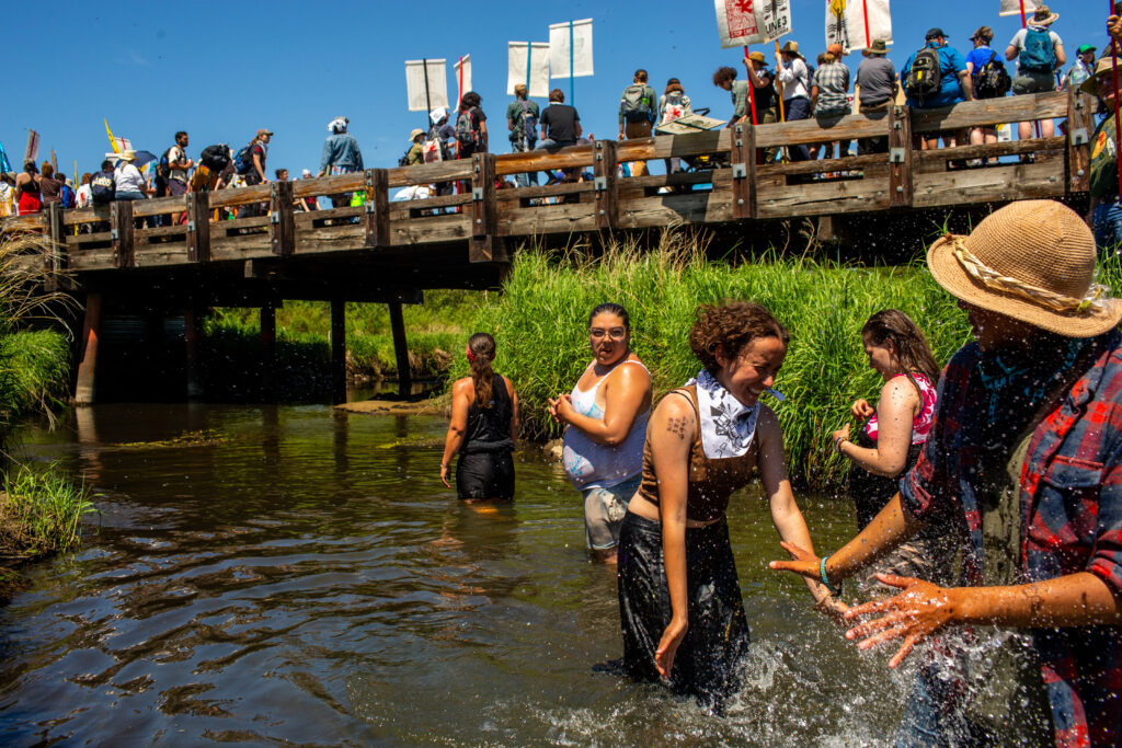 Demonstrators gather in the Mississippi River while others march across it during a 'Treaty People Gathering' protest in Clearwater County, Minnesota, on Monday, June 7, 2021. Credit: Nicole Neri/Bloomberg via Getty Images