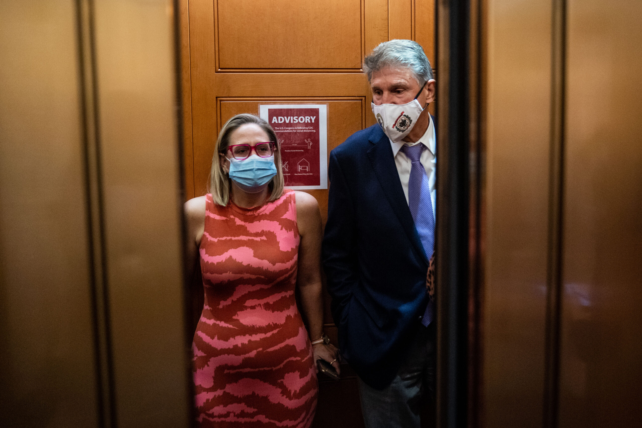 Sen. Kyrsten Sinema (D-Ariz.) and Sen. Joe Manchin (D-W.Va.) catch and an elevator to go to the Senate Chamber to vote, in the U.S. Capitol on Thursday, Sept. 30, 2021 in Washington, D.C. Credit: Kent Nishimura / Los Angeles Times via Getty Images
