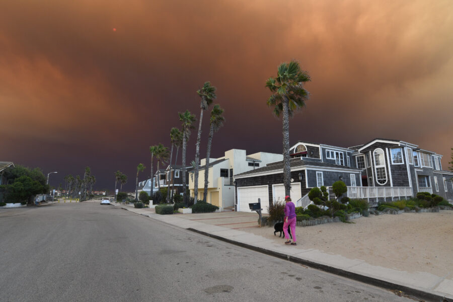 A woman walks her dog, under smoke from California fires on Nov. 9, 2018. Credit: Paul Harris/Getty Images