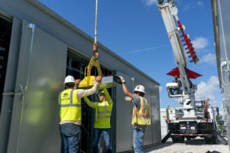 Workers install battery modules at the Manatee Energy Storage Center in Florida, being developed by Florida Power & Light. The project, on track to be complete by the end of the year, will have 409 megawatts of capacity, which would make it the largest battery storage project in the world by capacity. Photo Courtesy of Florida Power & Light