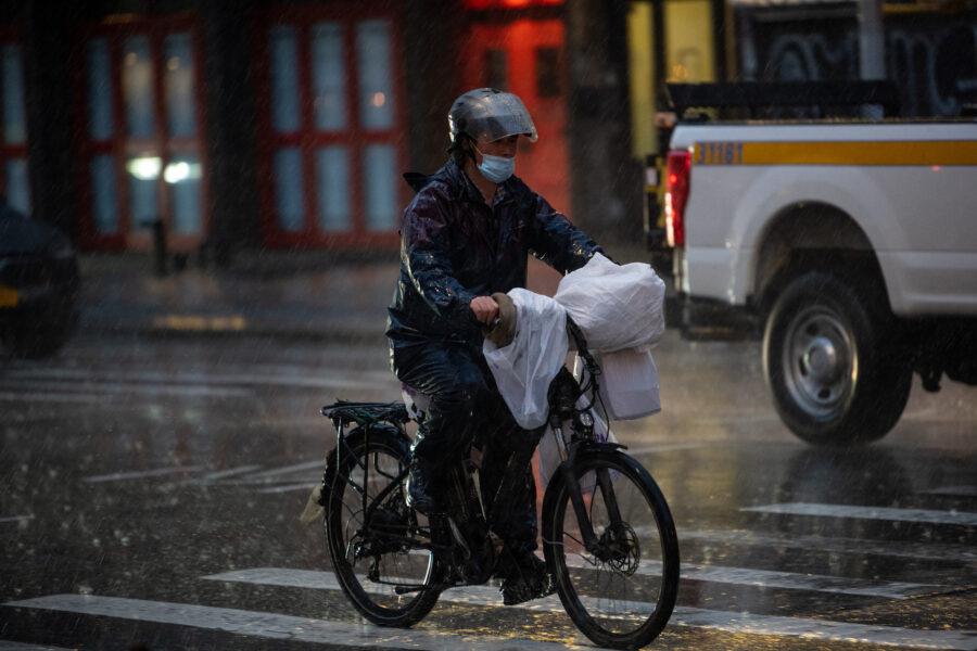A delivery driver rides a bicycle through the rain on March 24, 2021 in New York City. Credit: Alexi Rosenfeld/Getty Images