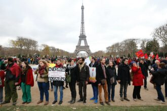 """A demonstrator holds a banner reading """"Energy liberate-ourselves from our fossil addictions"""" during a rally called by several NGOs to form a human chain near the Eiffel Tower in Paris on Dec. 12, 2015 on the sidelines of the COP21, the UN conference on global warming. Credit: Francois Guillot/AFP via Getty Images"""