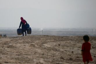 An Afghan girl carries empty containers to collect water, as a younger child looks on, in Sakhi village on the outskirts of Mazar-i-Sharif during a 2018 drought. Credit: Farshad Usyan/AFP via Getty Images