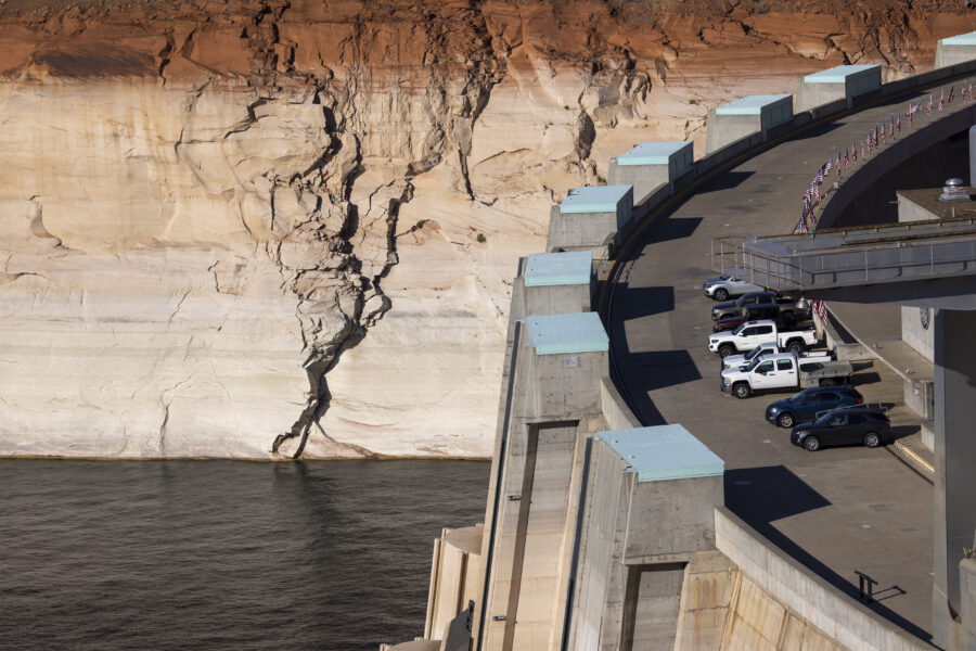 """Glen Canyon Dam is seen next to the white """"bathtub ring"""" of previously submerged rock, indicating record low water levels at Lake Powell as the drought continues to worsen on July 2, 2021 near Page, Arizona. Credit: David McNew/Getty Images"""