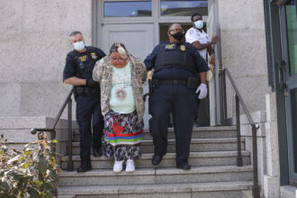 Police officers escort a protester out of the Department of Interior building after a sit-in held by climate activists on Oct. 14, 2021 in Washington, DC. Credit: Kevin Dietsch/Getty Images